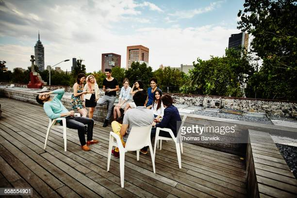 laughing friends gathered sharing drinks on deck - county stock pictures, royalty-free photos & images
