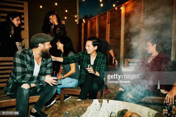 laughing friends hanging out around fire in backyard on summer evening - barbecue social gathering stock pictures, royalty-free photos & images