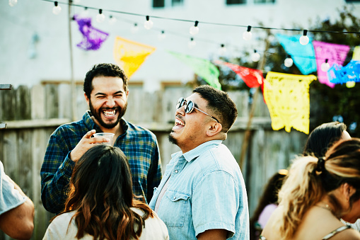 Laughing friends hanging out during backyard barbecue on summer evening - gettyimageskorea
