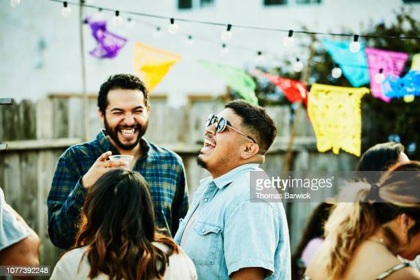 laughing friends hanging out during backyard barbecue on summer evening - barbecue social gathering stock pictures, royalty-free photos & images