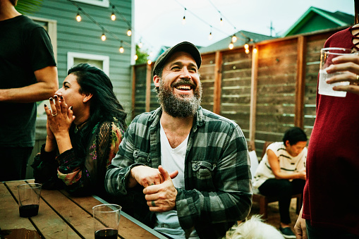 Laughing friends hanging out together during backyard dinner party - gettyimageskorea