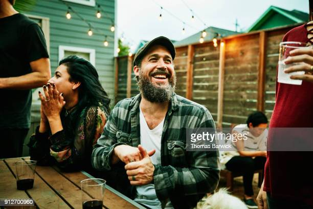 laughing friends hanging out together during backyard dinner party - southern usa stock pictures, royalty-free photos & images