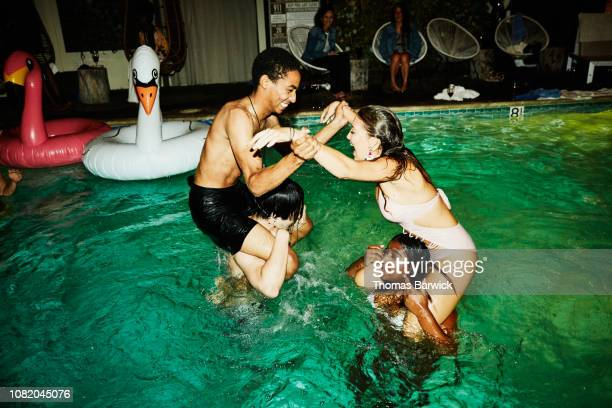 laughing friends having chicken fight in hotel pool during party - mixed wrestling stockfoto's en -beelden