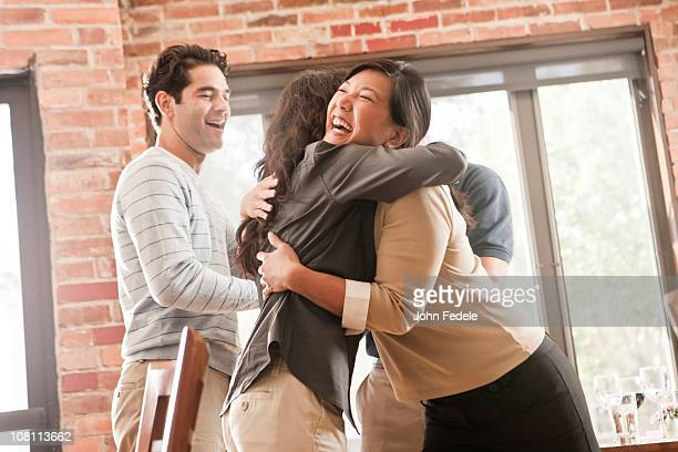 Laughing friends hugging