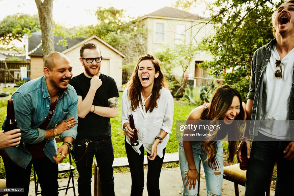 Laughing  friends in backyard on summer evening : Stock Photo