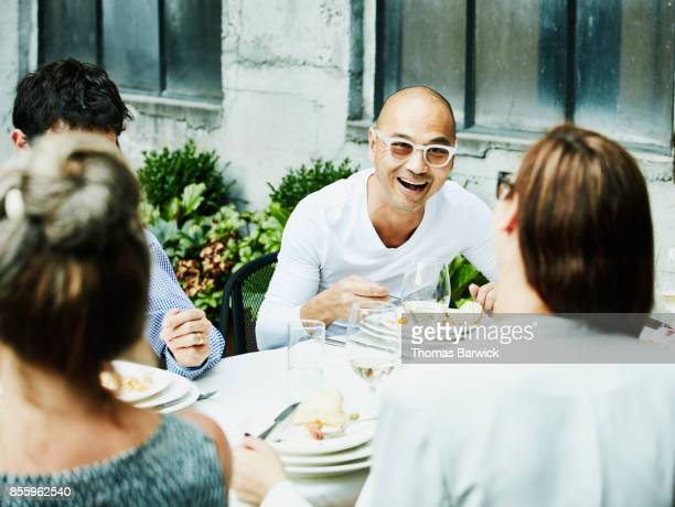 Laughing friends in discussion during dinner on outdoor patio