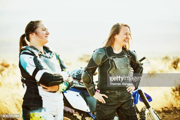 Laughing friends in discussion while resting during desert dirt bike ride