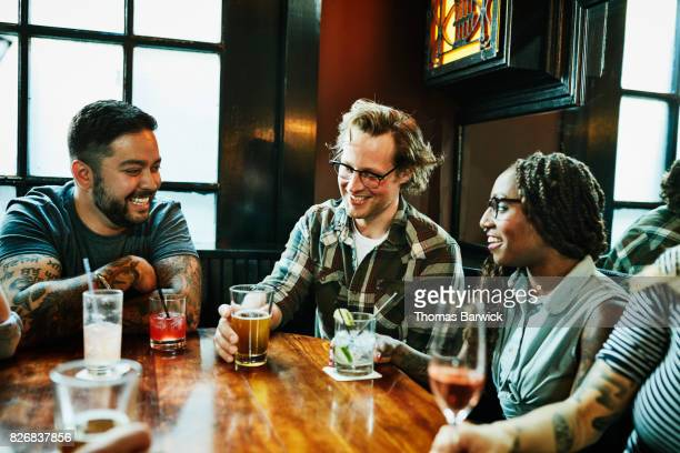 laughing friends in discussion while sharing drinks at table in bar - kneipe stock-fotos und bilder