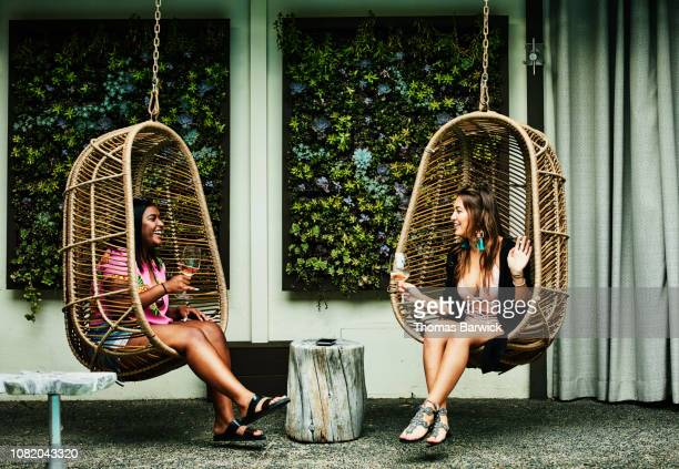 laughing friends in discussion while sitting in hanging chairs during pool party - weekend activities stock pictures, royalty-free photos & images