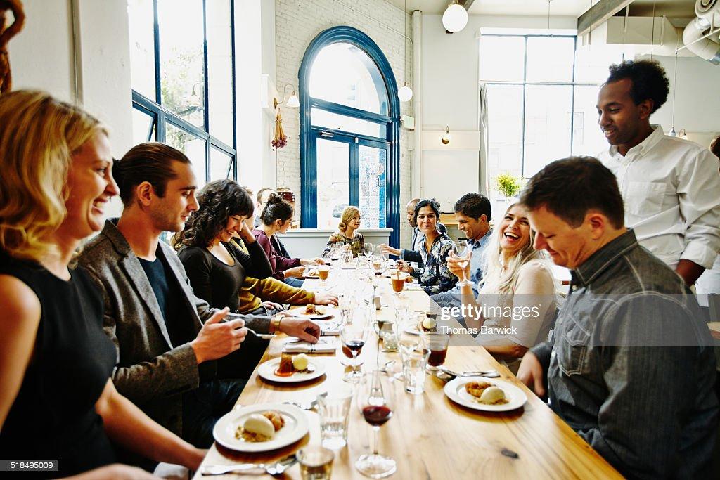 Laughing friends in restaurant eating dessert : Stock Photo