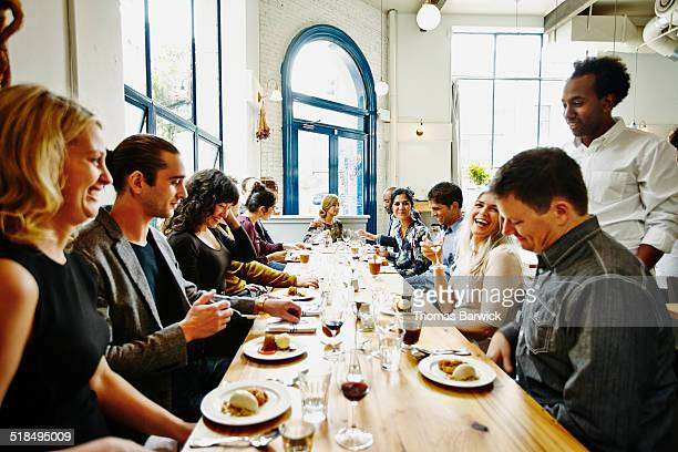 laughing friends in restaurant eating dessert - mid adult stock pictures, royalty-free photos & images