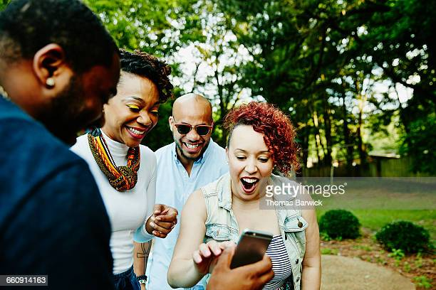 Laughing friends looking at photo on smartphone