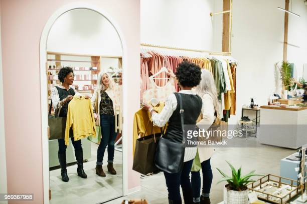 laughing friends looking at tops in mirror during shopping trip in clothing boutique - older women in short skirts stock pictures, royalty-free photos & images