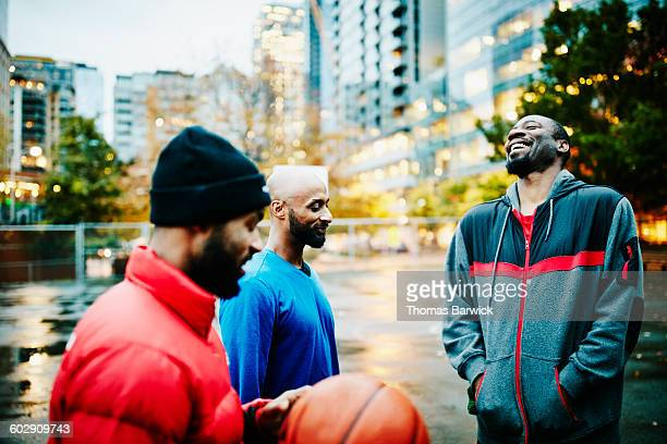 Laughing friends on basketball court before game