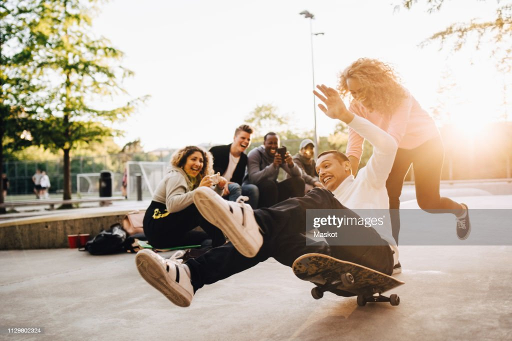 Laughing friends photographing man falling from skateboard while woman pushing him at park : Stock Photo