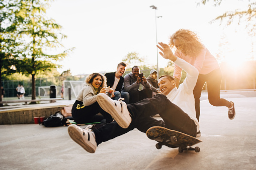 Laughing friends photographing man falling from skateboard while woman pushing him at park - gettyimageskorea