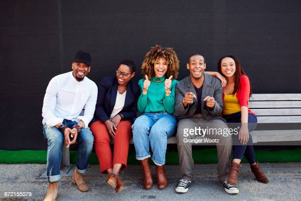Laughing friends posing on bench