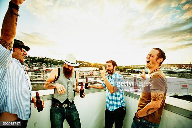 Laughing friends sharing beers on rooftop