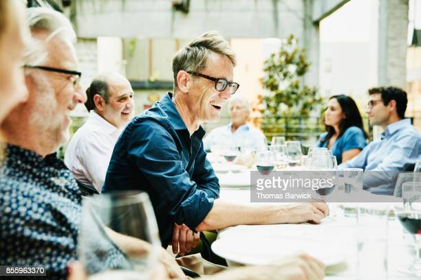 laughing friends sharing celebration dinner on restaurant patio - mid adult men stock-fotos und bilder