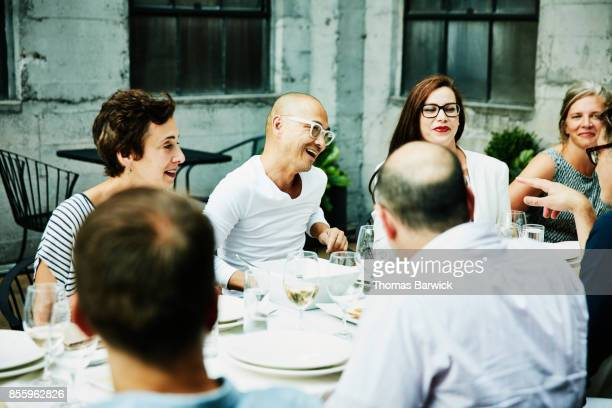 Laughing friends sharing celebration meal on outdoor patio