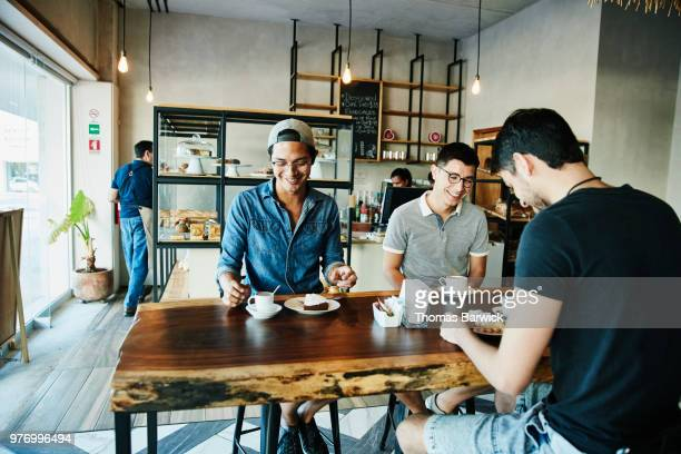 laughing friends sharing coffee and pastries at table in bakery - só homens jovens imagens e fotografias de stock