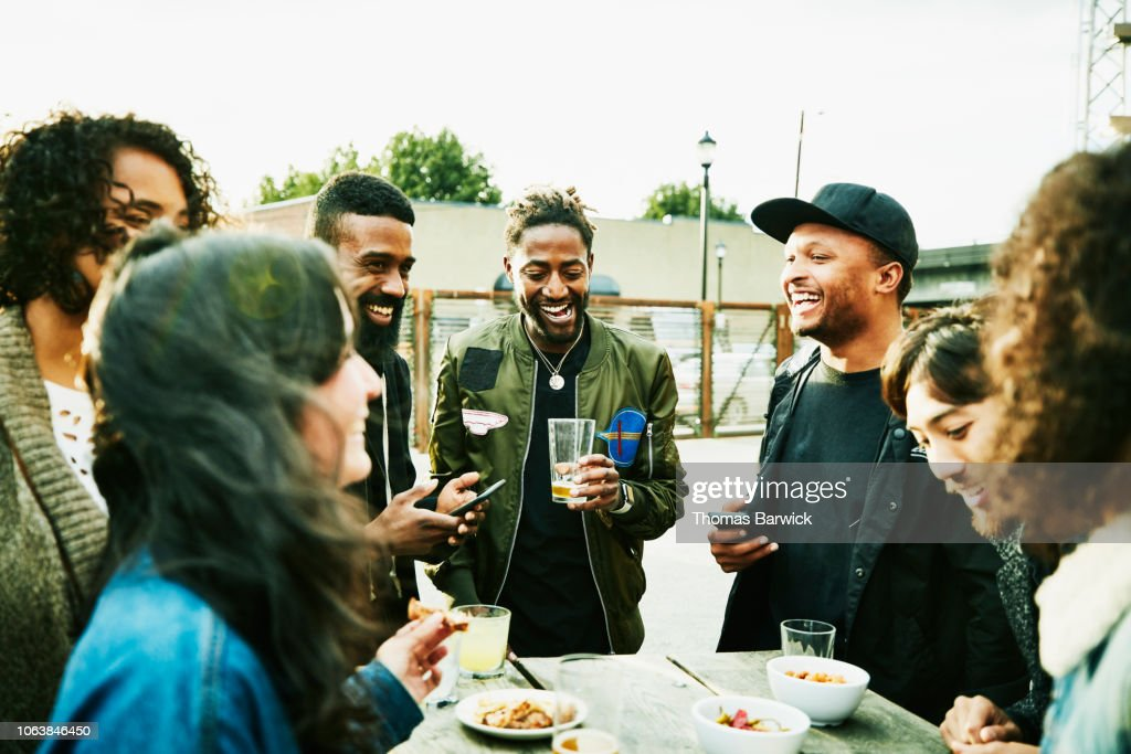 Laughing friends sharing drinks and food at outdoor bar : Stock Photo