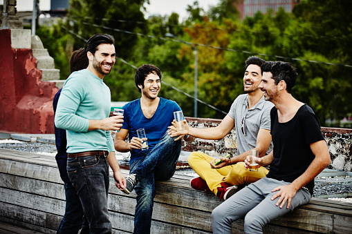 Laughing friends sharing drinks on deck - gettyimageskorea