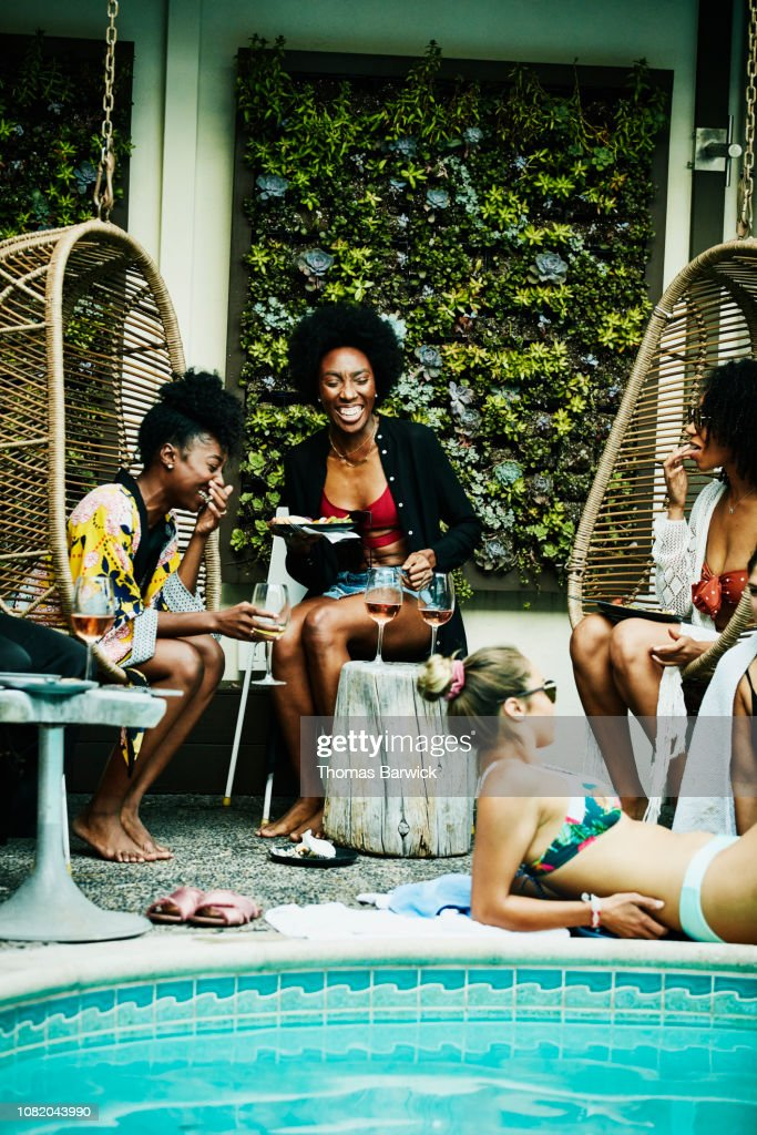 Laughing friends sharing food and drink during party at hotel pool : Stock Photo