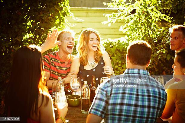 Laughing friends sitting at table in backyard