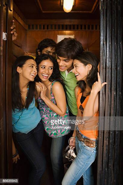 Laughing friends standing in doorway