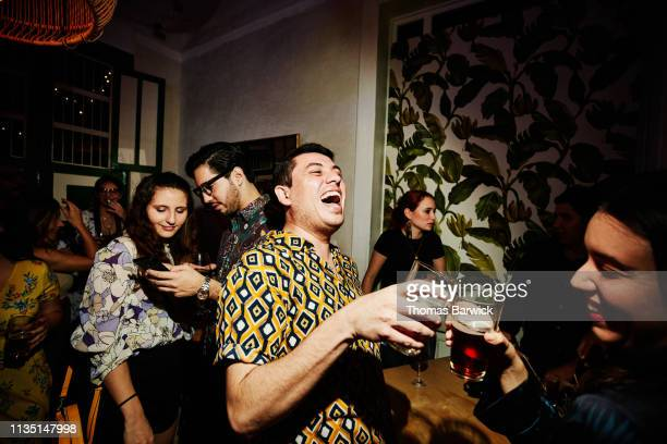 laughing friends toasting during party in night club - dancing stockfoto's en -beelden