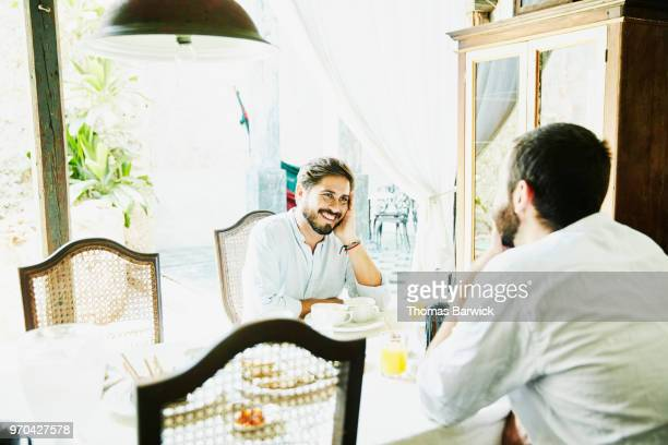Laughing gay couple in discussion while sharing breakfast in courtyard of boutique hotel