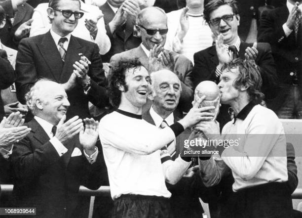 Laughing German captain Franz Beckenbauer and goalkeeper Sepp Maier hold the just won World Cup trophy with Maier even kissing it. On the left,...