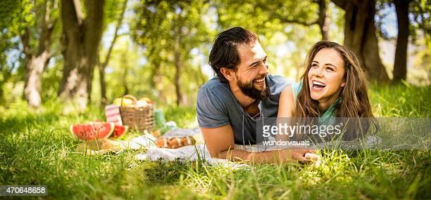 Rir menina e seu namorado um piquenique relaxante no parque