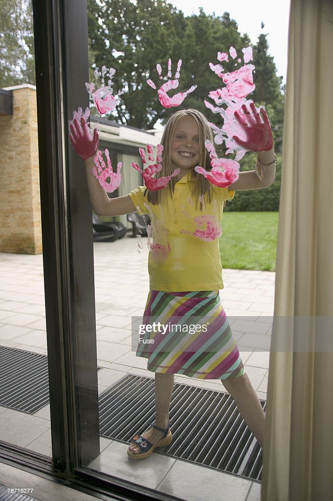 Laughing girl hand painting window pane : Stock Photo