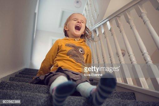 Laughing girl (4-5) having fun sliding down carpeted stairs