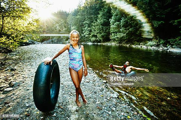 Laughing girl holding inner tube standing by river