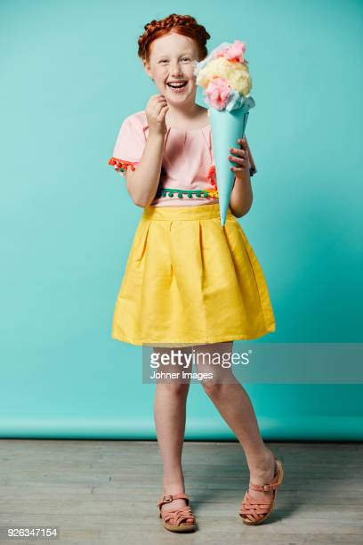 Laughing girl holding toy ice-cream cone