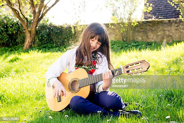 Laughing girl sitting on a meadow playing guitar