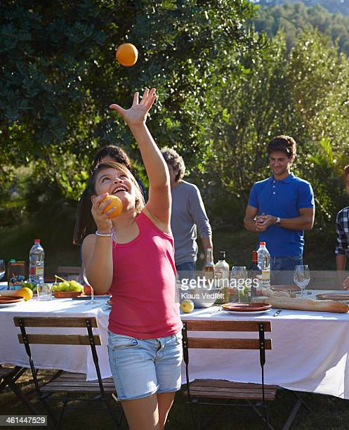 Laughing girl throwing oranges up in the air