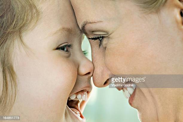 A laughing girl touching noses with her smiling mother, close-up