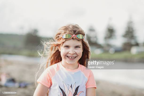 laughing girl wearing rashie and googles at the beach - google stock pictures, royalty-free photos & images