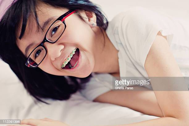 Laughing girl with braces and glasses