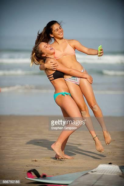 "laughing girls doing ""selfies"" on the beach - solo bambine femmine costume da bagno foto e immagini stock"