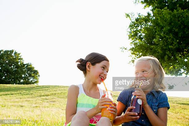 Laughing girls drinking juice outdoors