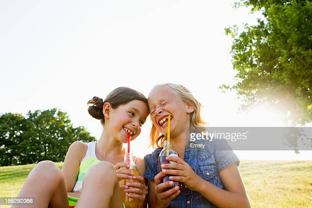 Laughing girls drinking juice outdoors