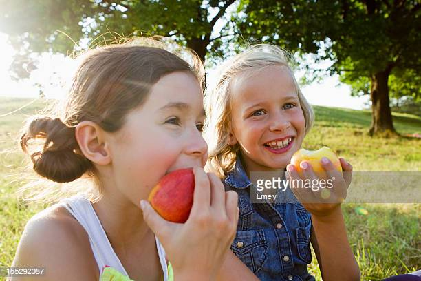 laughing girls eating apples outdoors - apple fruit stock photos and pictures