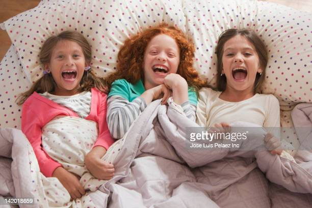 Laughing girls laying in bed together