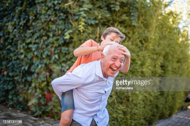 laughing grandfather giving playful grandson piggyback ride - piggyback stock pictures, royalty-free photos & images