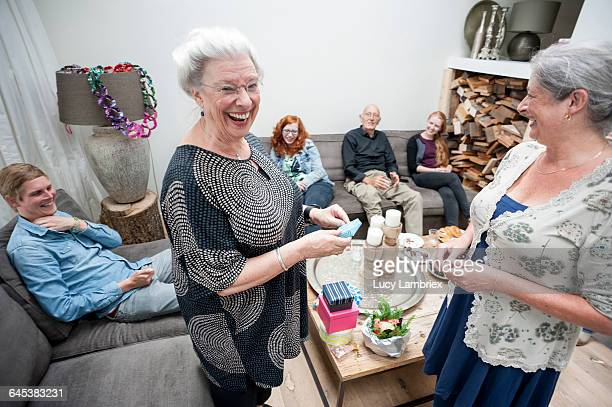 Laughing grandmother receiving birthday gift
